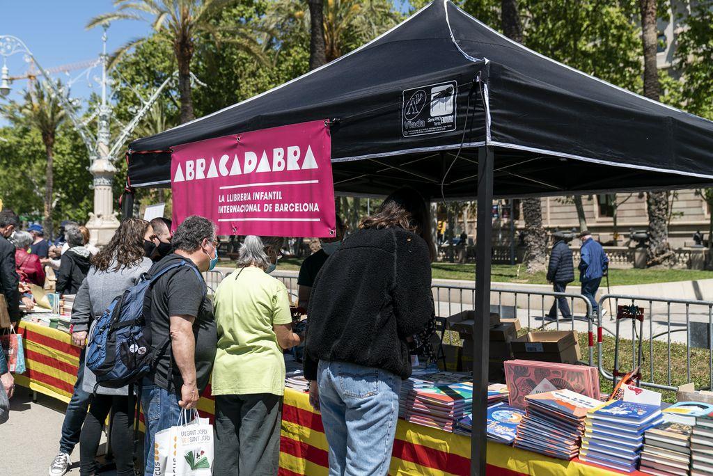 Compradors fullegen i compren llibres a la parada d'una llibreria especialitzada en literatura infantil instal·lada al recinte firal del passeig de Lluís Companys amb motiu de la diada de Sant Jordi