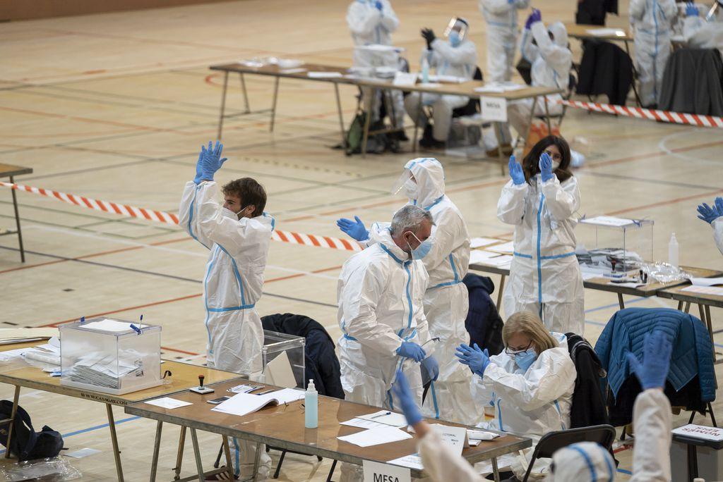 Els membres de les meses electorals situades al Centre Esportiu Municipal L'Espanya Industrial aplaudeixen un cop finalitzades les votacions de la jornada electoral del 14-F
