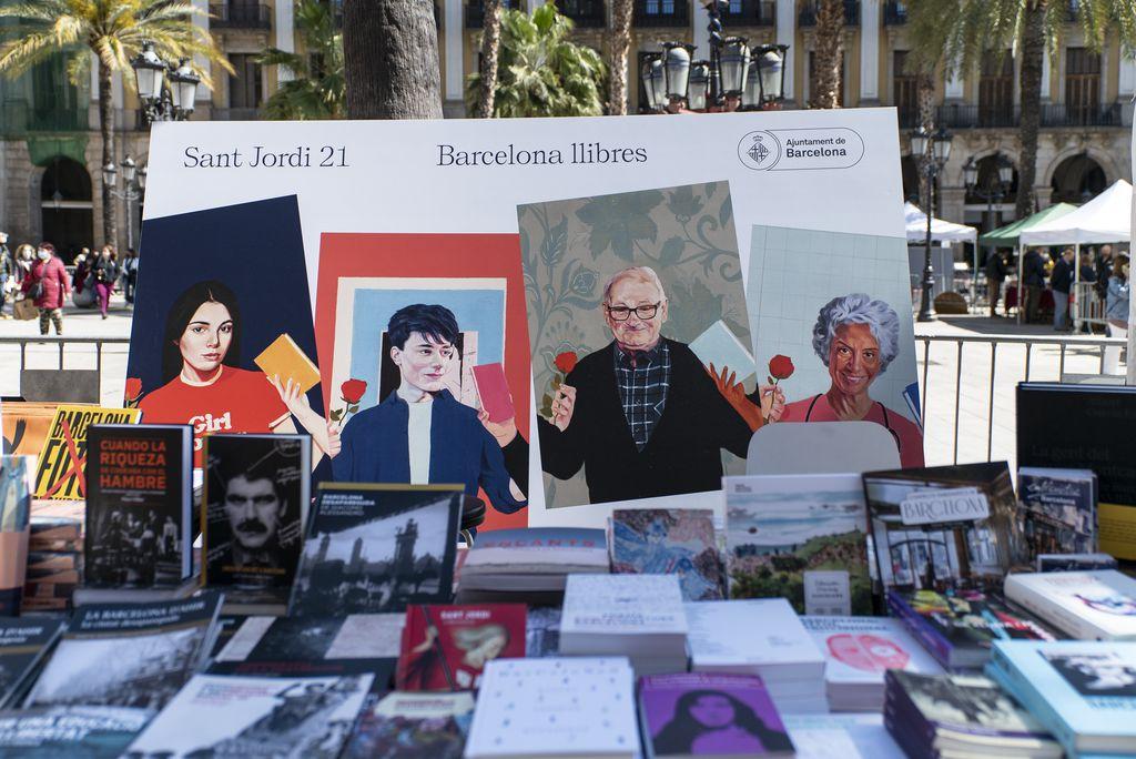 Parada de llibres dels Serveis Editorials de l'Ajuntament on es mostren les publicacions pròpies. Al darrere, el cartell de la campanya de Sant Jordi 2021
