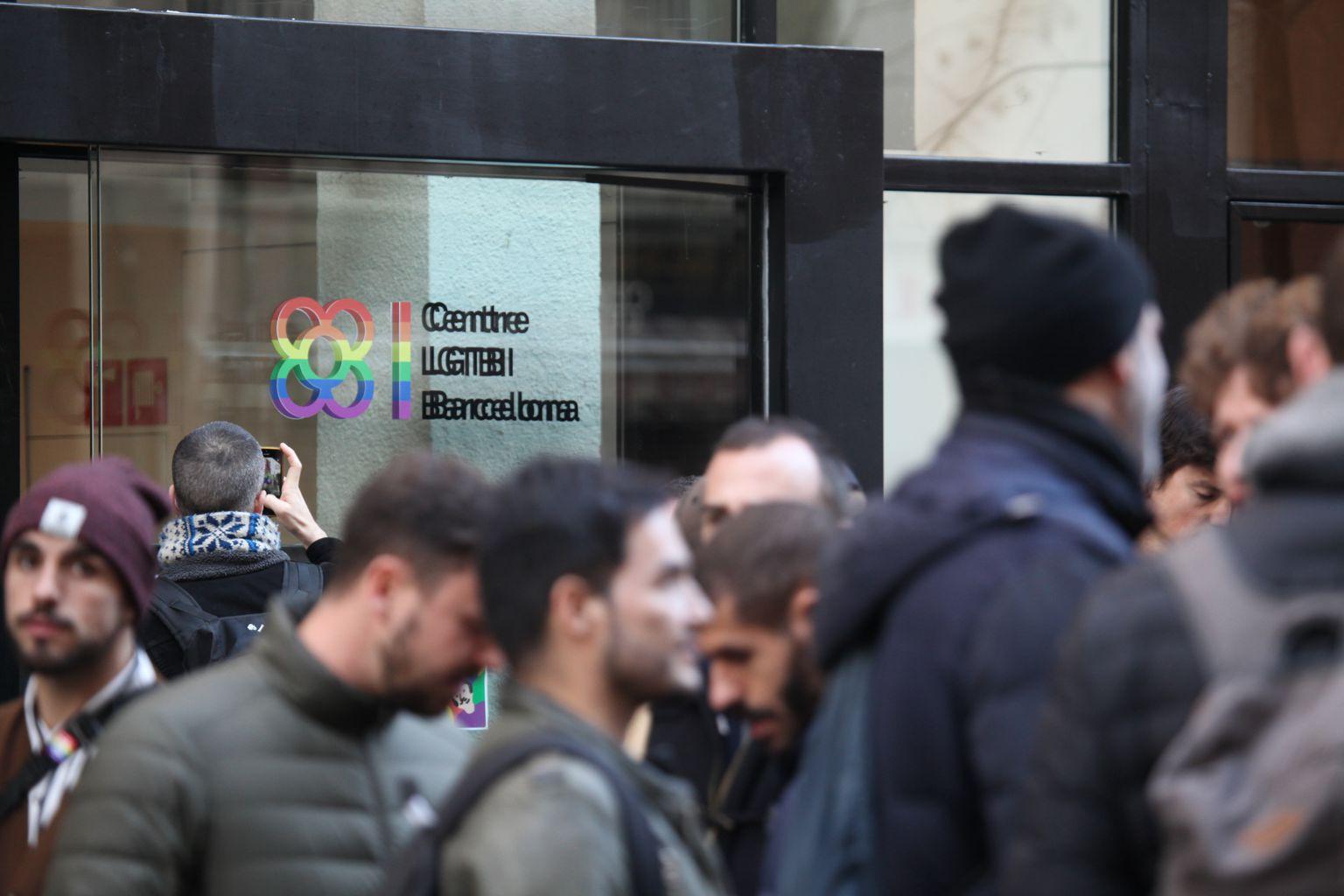 Porta d'entrada del Centre LGTBI de Barcelona amb persones a l'exterior esperant per entrar