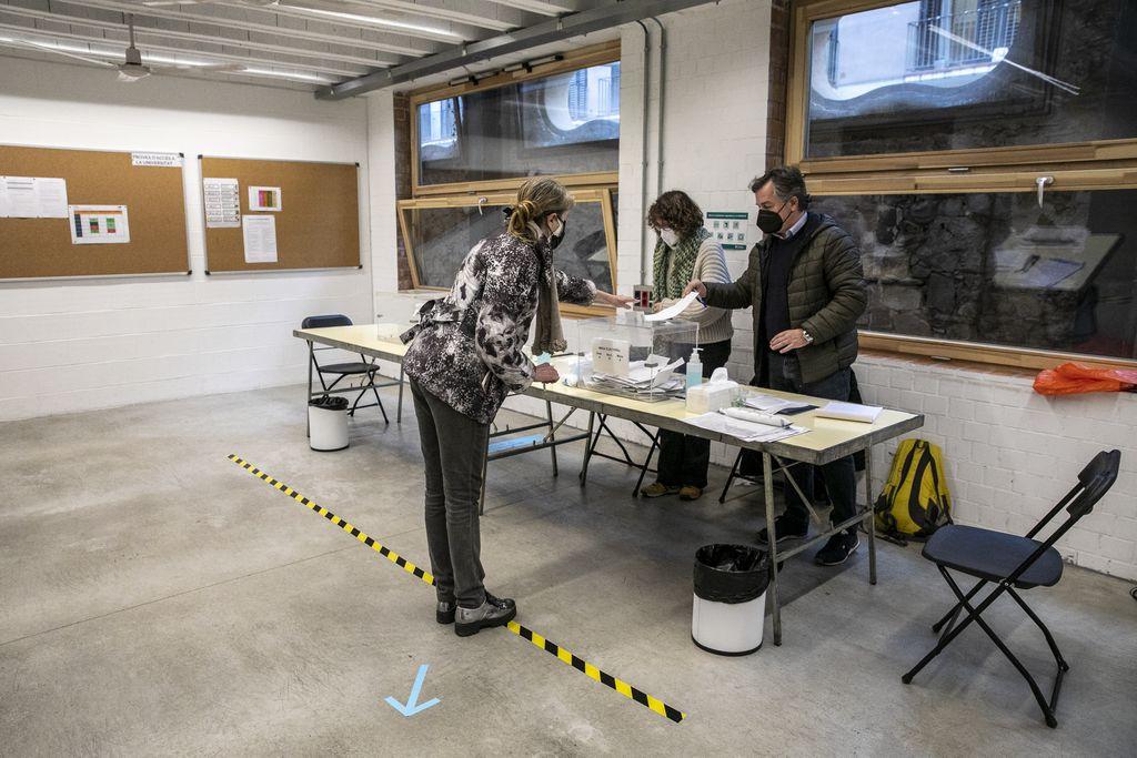 A les Cristalleries Planell, una dona vota a una de les meses i intenta mantenir la distància de seguretat marcada davant de la taula on està situada l'urna