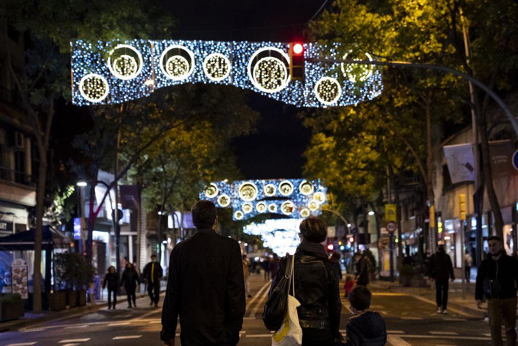 """Una família passeja sota els llums de Nadal del carrer de la Creu Coberta aprofitant que està tancat al trànsit durant l'""""Obrim carrers"""""""
