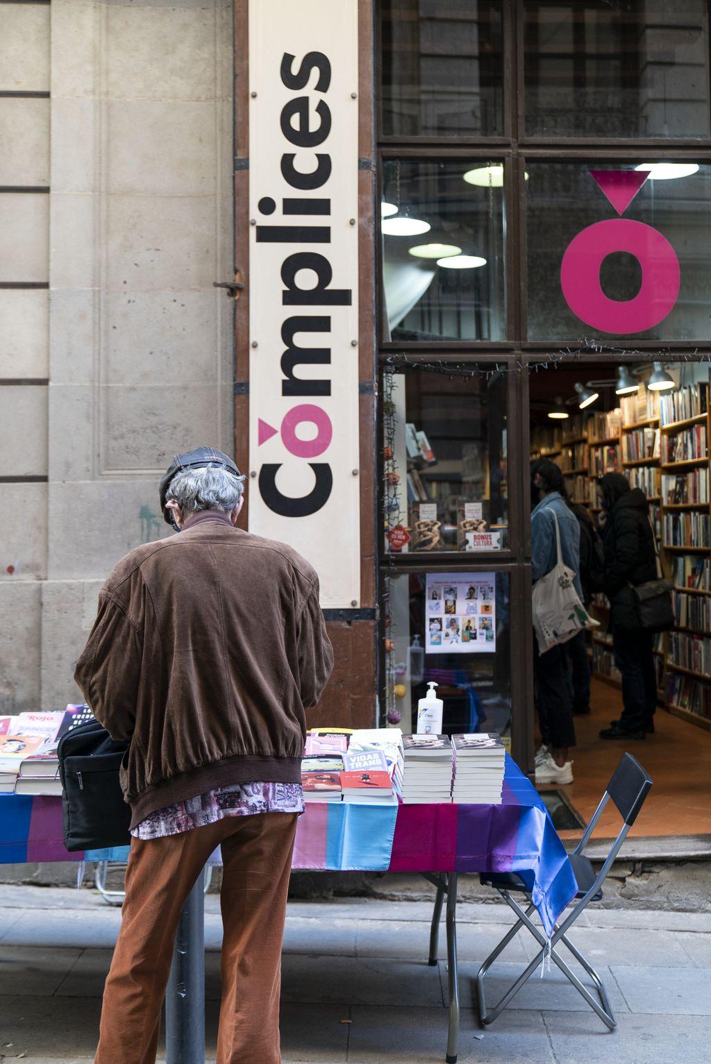 Un home mira els llibres de la parada davant de la llibreria Cómplices muntada amb motiu de la diada de Sant Jordi. A l'interior de la botiga també es veuen clients comprant i fullejant llibres