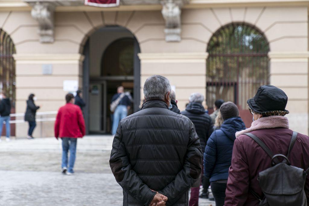 Persones que fan cua a l'exterior de la seu del districte de Sant Martí on hi ha instal·lat un dels col·legis electorals del 14-F