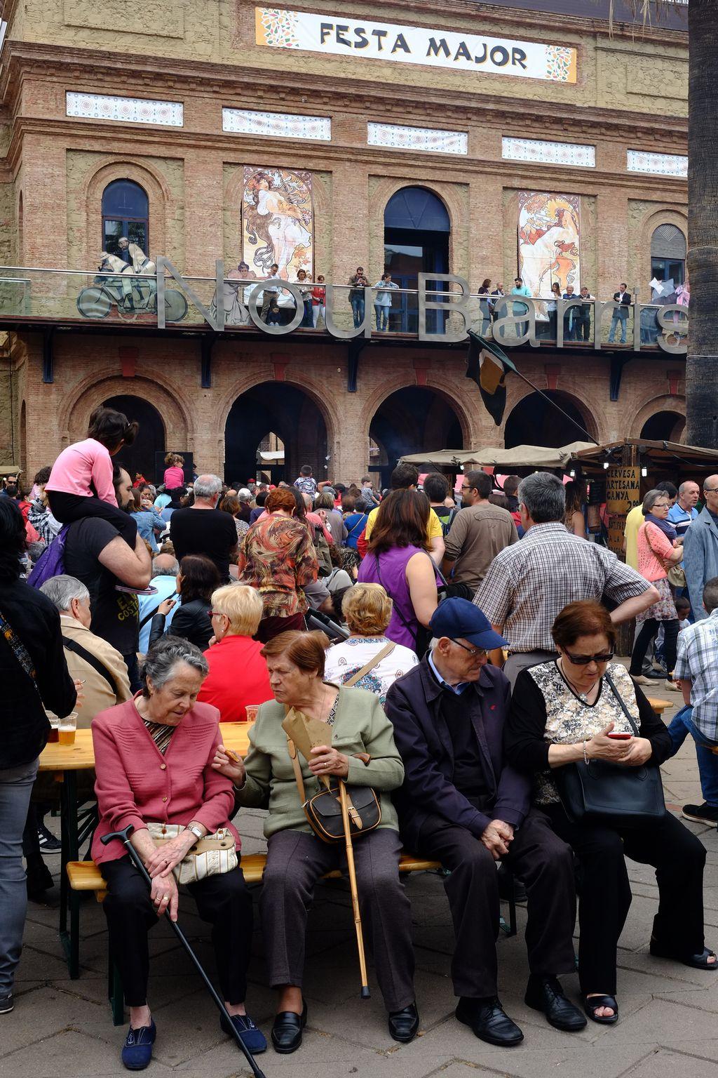 Festa Major de Nou Barris. Gent gran descansant durant el mercat de productes artesanals