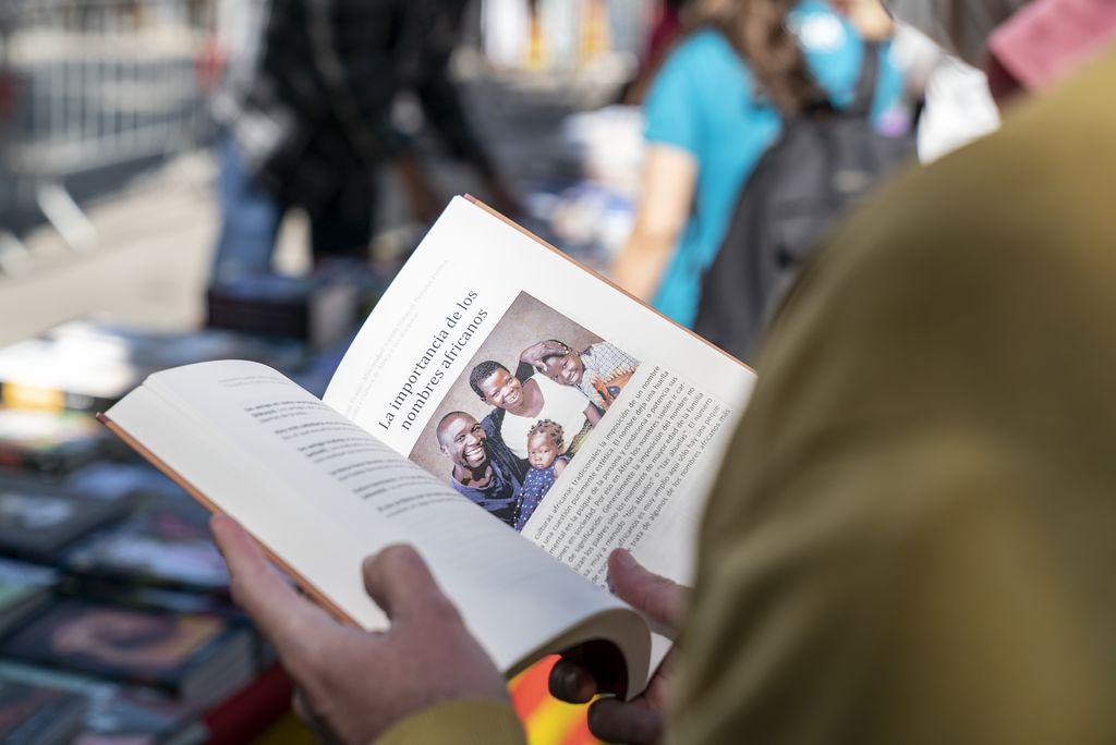 Una persona fulleja un llibre en una parada muntada a la plaça Reial amb motiu de la diada de Sant Jordi