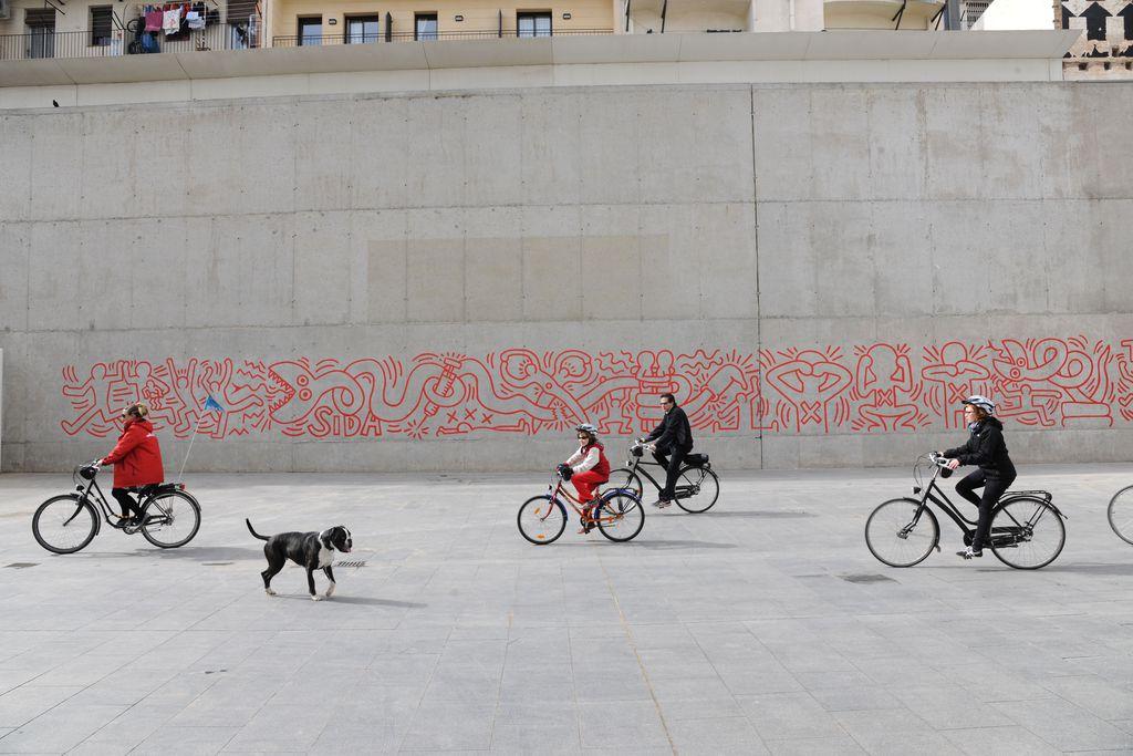 Mural contra la sida de Keith Haring. Ciclistes passant per davant del mural