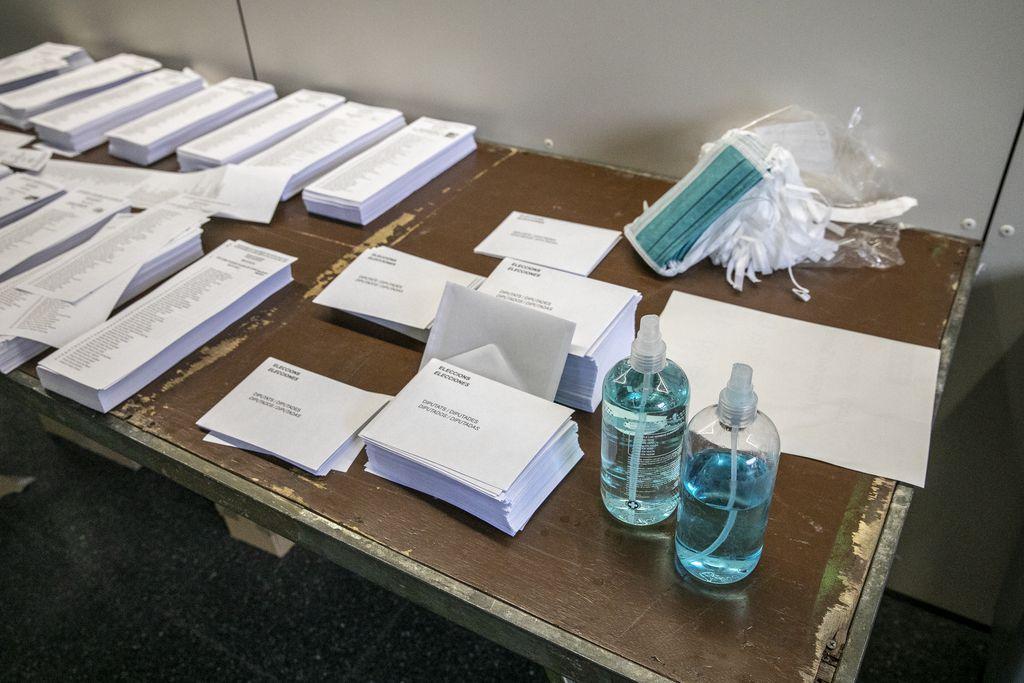Taula amb mascaretes, paperetes, sobres i gel hidroalcohòlic per als votants del Mercat de Sant Antoni