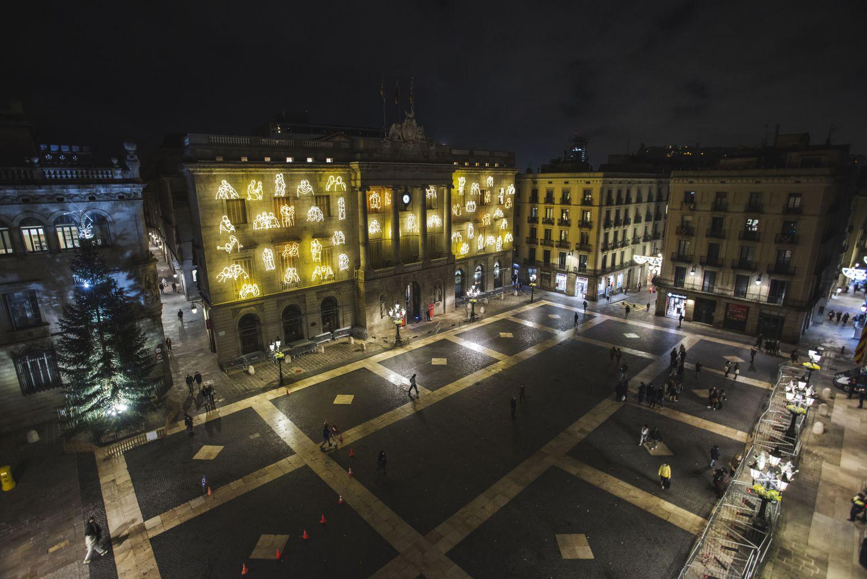Vista de la plaça de Sant Jaume amb la façana de l'Ajuntament il·luminada amb escenes quotidianes de Ciutat Vella, una obra del col·lectiu RavalKm#0 amb motiu de les festes de Nadal. Al costat, es veu l'arbre de Nadal