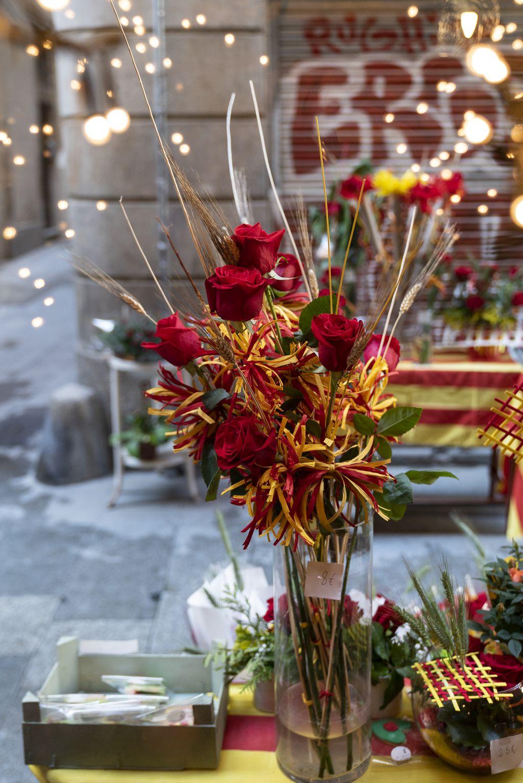 Roses en un gerro i centres amb roses a l'aparador d'una floristeria el dia de Sant Jordi