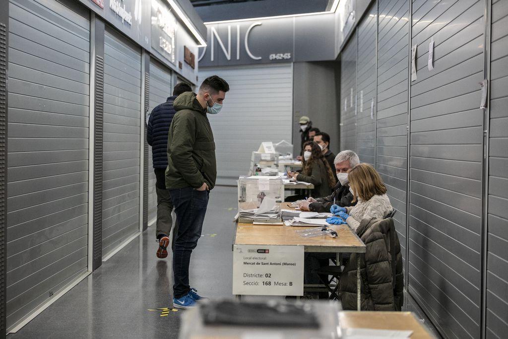 Un home està votant a una de les meses de l'interior del Mercat de Sant Antoni