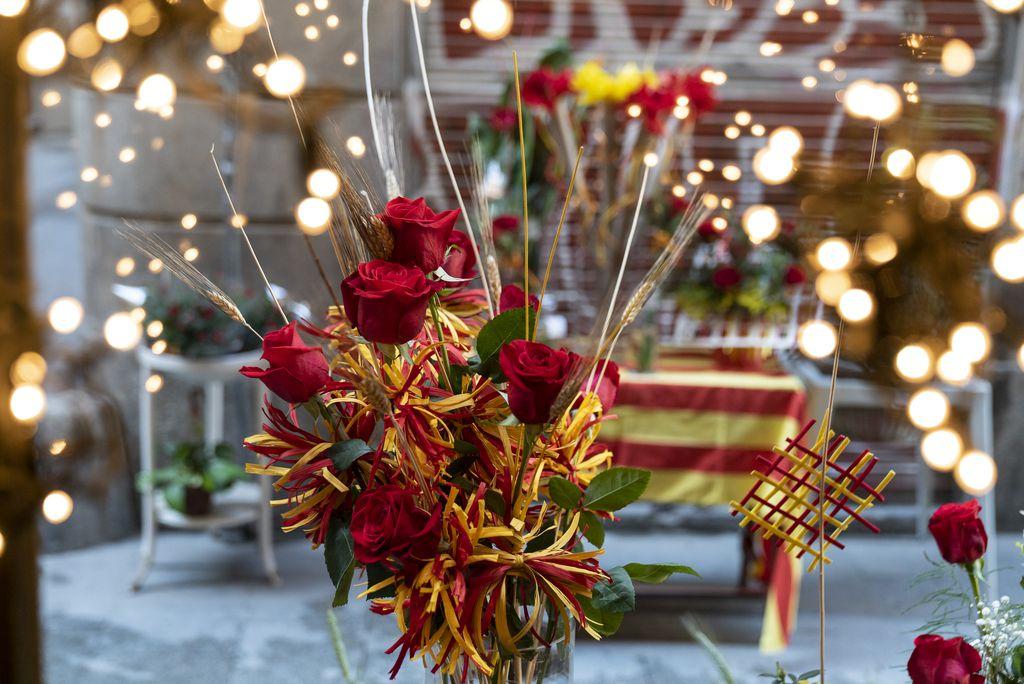 Roses amb espigues i decoració en groc i vermell a l'aparador d'una floristeria amb motiu de la diada de Sant Jordi