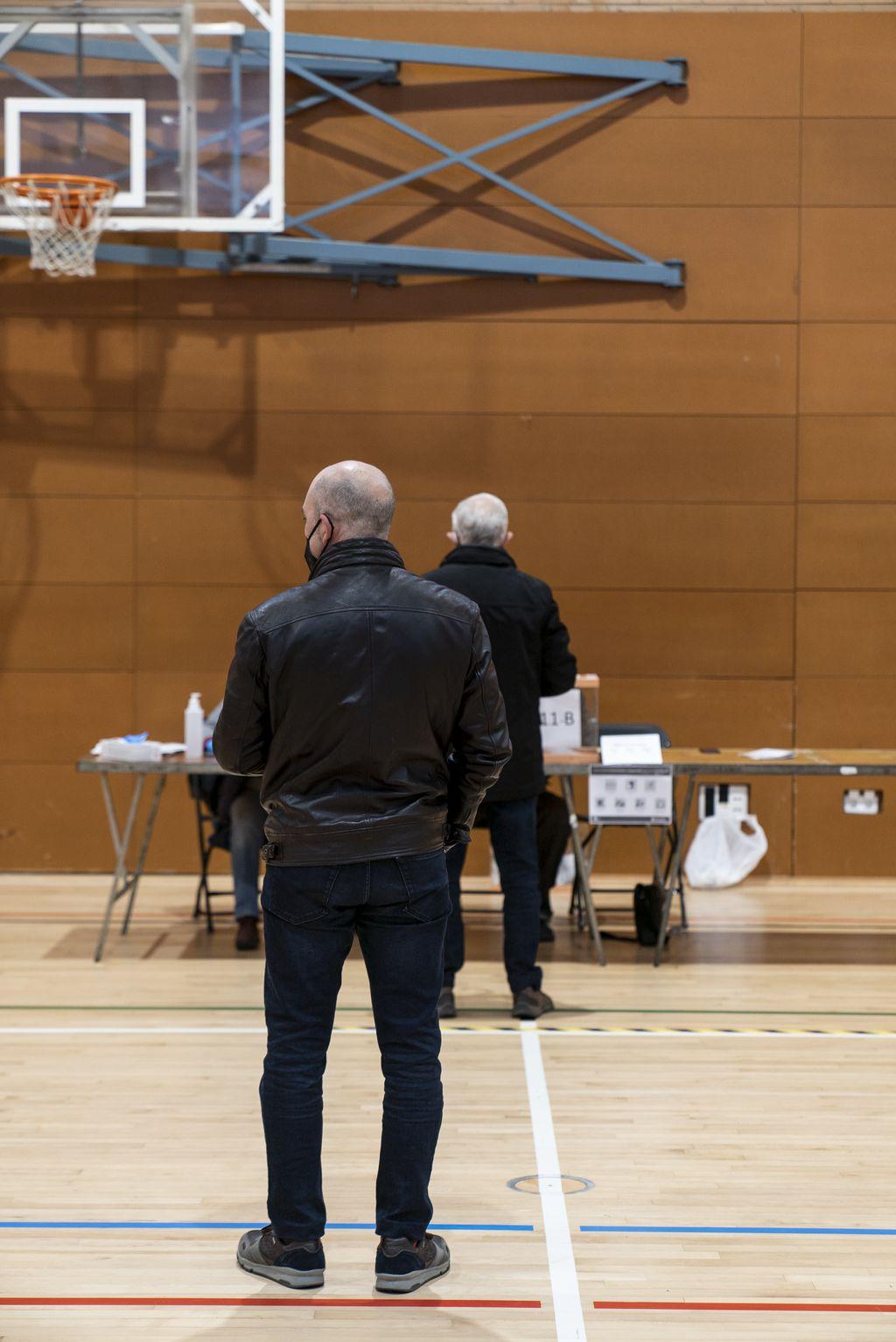 Cua de votants a l'interior del Poliesportiu Virrei Amat, on hi ha una persona que està votant i una altra que s'espera amb la distància de seguretat