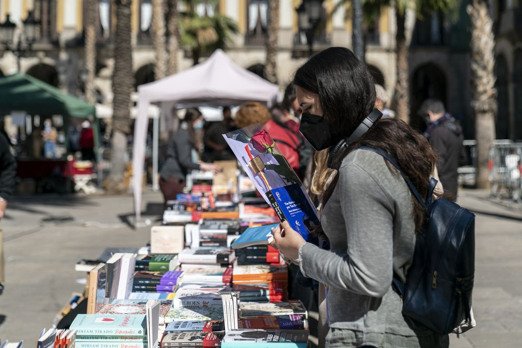 Una jove amb una rosa a la mà mira llibres en una parada de la plaça Reial, un dels espais firals habilitats per celebrar la diada de Sant Jordi