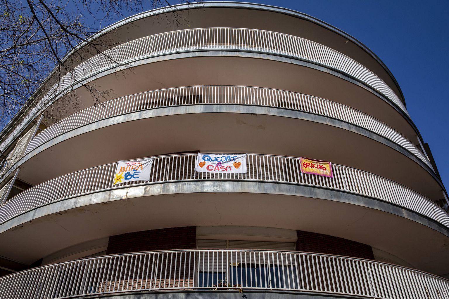 """Edifici de la plaça de Comas amb pancartes """"Tot anirà bé"""", """"Queda't a casa"""" i """"Gracias"""". Districte de les Corts."""