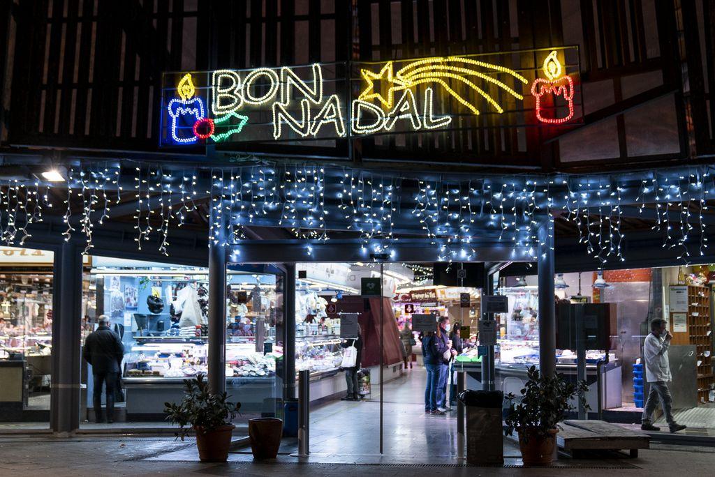 Decoració nadalenca exterior del Mercat de Sants amb garlandes de llums blaus i un rètol de llums de colors que diu bon Nadal. A l'interior es veuen les parades i la gent comprant
