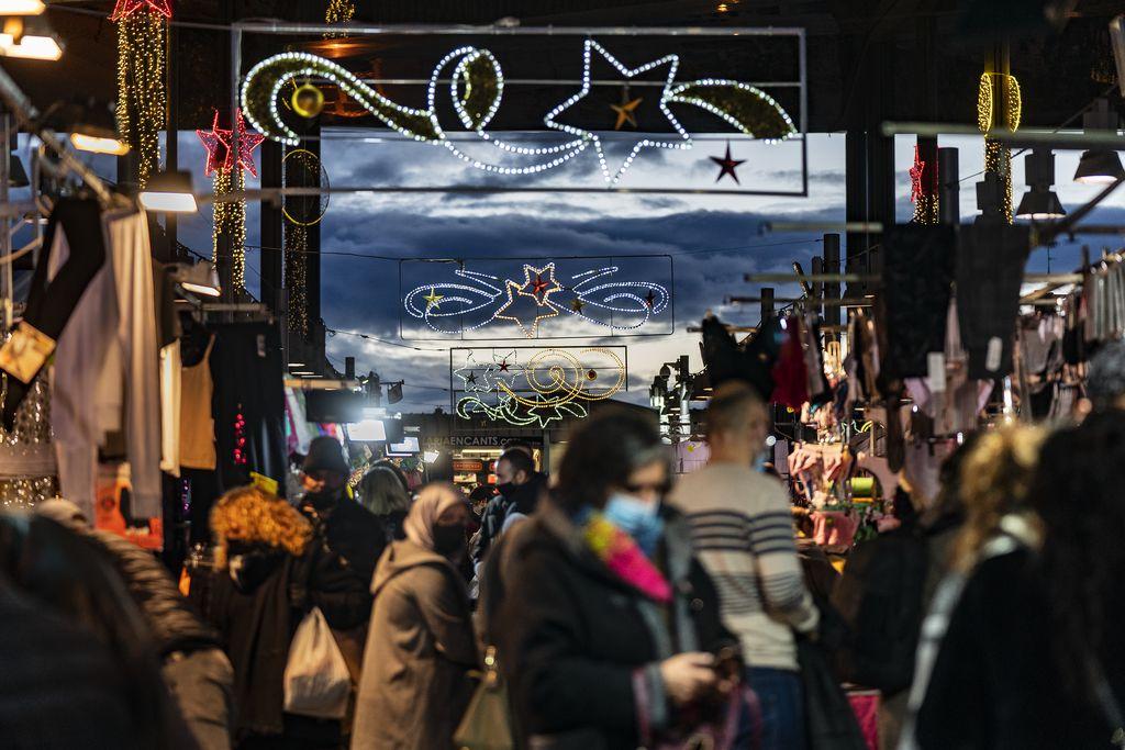 Gent comprant al capvespre al Mercat dels Encants, quan els llums de Nadal de l'equipament es comencen a encendre