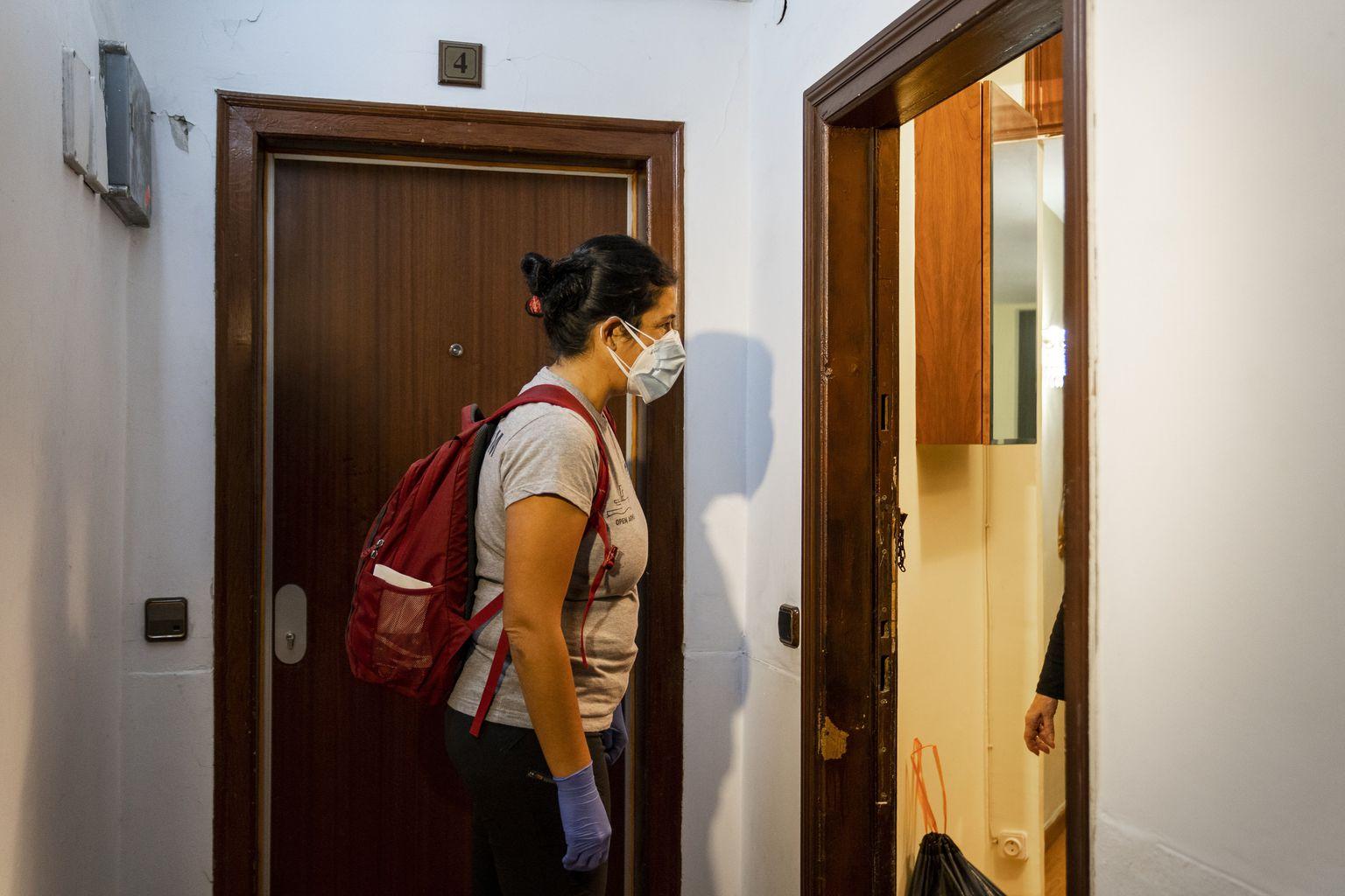 Una membre de l'ONG Open Arms, degudament protegida amb guants i mascareta, al replà d'un edifici on una dona li obre la porta