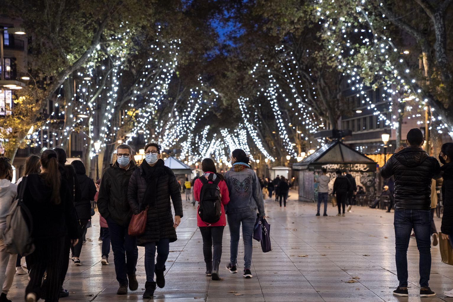 Gent passejant per La Rambla sota els llums de Nadal encesos