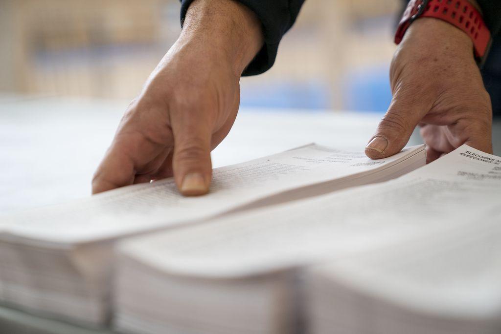 Un dels treballadors municipals del dispositiu electoral col·loca les paperetes sobre una taula al Poliesportiu Municipal Camp del Ferro